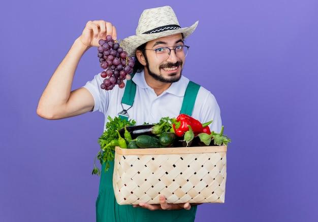 Joven jardinero barbudo hombre vestido con mono y sombrero sosteniendo cajón lleno de verduras mostrando racimo de uva sonriendo de pie sobre la pared azul