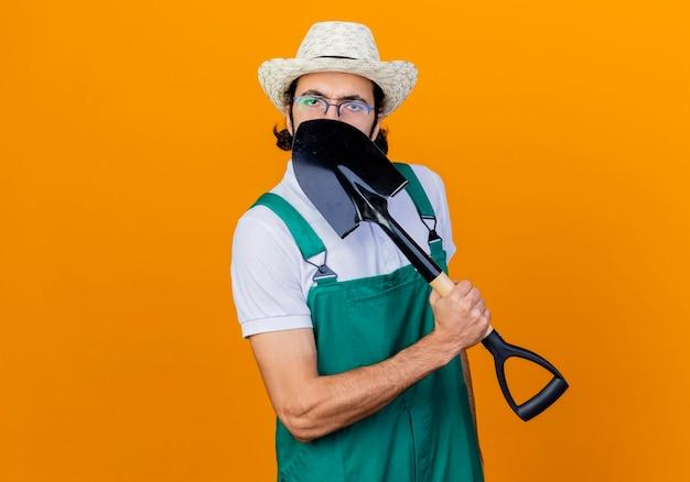 Joven jardinero barbudo hombre vestido con mono y sombrero sosteniendo la pala de pie sobre la pared naranja ocultando su rostro asomando