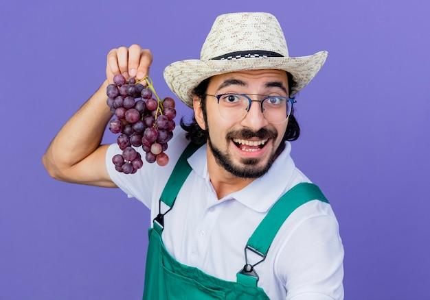 Joven jardinero barbudo hombre vestido con mono y sombrero sosteniendo racimo de uva mirando al frente sonriendo de pie sobre la pared azul
