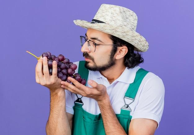 Joven jardinero barbudo hombre vestido con mono y sombrero sosteniendo racimo de uva mirándolo de pie sobre la pared azul