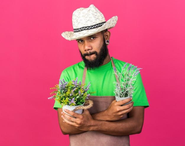 Joven jardinero codicioso chico afroamericano con sombrero de jardinería sosteniendo y cruzando flores en maceta