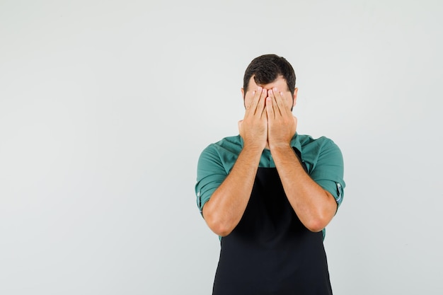 Joven jardinero cogidos de la mano en la cara en camiseta, delantal y mirando llorando, vista frontal.