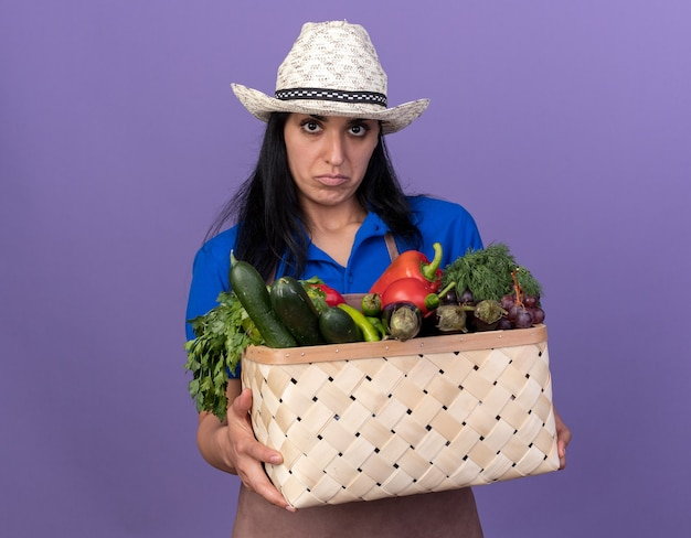 Joven jardinero confundido vistiendo uniforme y sombrero sosteniendo una canasta de verduras mirando al frente aislado en la pared púrpura con espacio de copia