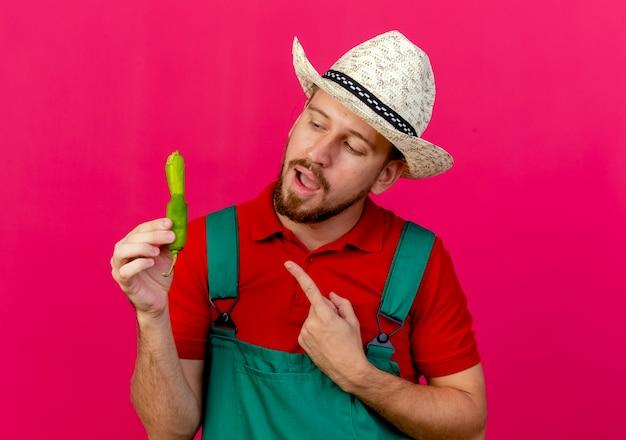 Joven jardinero eslavo guapo en uniforme y sombrero sosteniendo y mirando pimienta apuntando a explicar algo