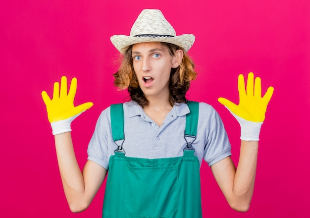 Joven jardinero hombre vestido con mono y sombrero con guantes de goma levantando las palmas
