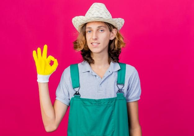 Joven jardinero hombre vestido con mono y sombrero con guantes de goma sonriendo mostrando signo ok