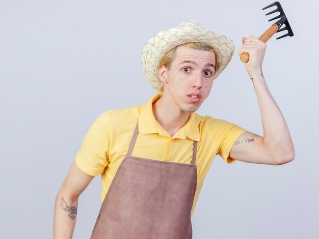 Joven jardinero hombre vestido con mono y sombrero mini rastrillo balanceándose confundido