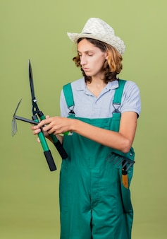 Joven jardinero hombre vestido con mono y sombrero sosteniendo cortasetos