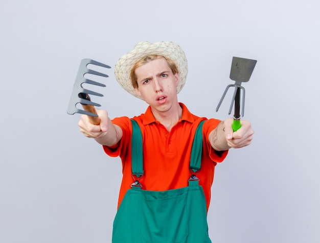 Joven jardinero hombre vestido con mono y sombrero sosteniendo mini rastrillo y azadón disgustado