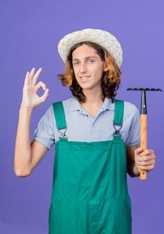 Joven jardinero hombre vestido con mono y sombrero sosteniendo mini rastrillo sonriendo