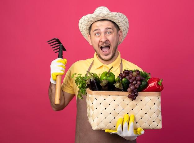 Joven jardinero vistiendo mono y sombrero en guantes de trabajo sosteniendo una caja llena de verduras con un mini rastrillo gritando emocionado y feliz parado sobre una pared rosa