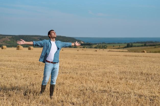 Joven en jeans, camisa, botas de goma en el campo con las manos abiertas