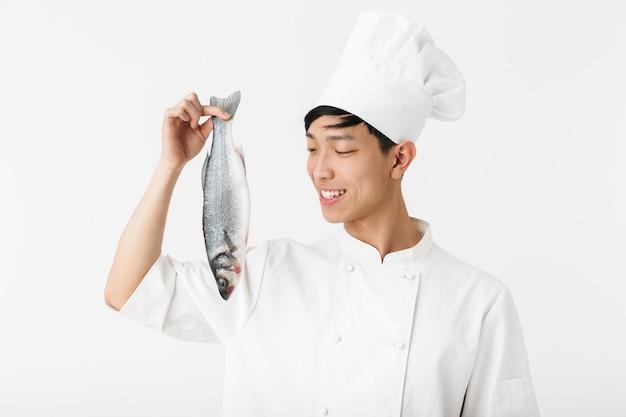 Joven jefe positivo en uniforme de cocinero blanco y sombrero sonriendo mientras sostiene pescado fresco crudo aislado sobre una pared blanca
