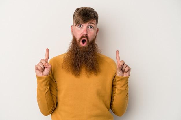 Joven jengibre caucásico con barba larga aislado sobre fondo blanco apuntando al revés con la boca abierta.