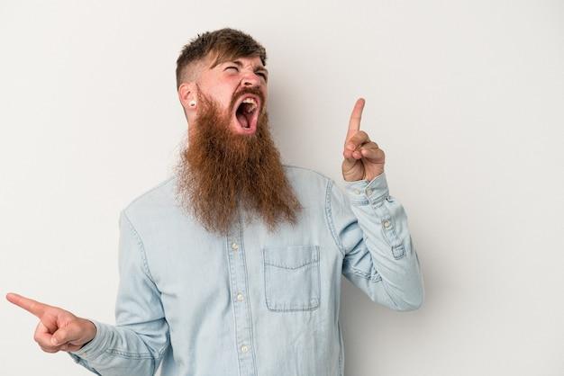 Joven jengibre caucásico con barba larga aislado sobre fondo blanco apuntando a diferentes espacios de copia, eligiendo uno de ellos, mostrando con el dedo.