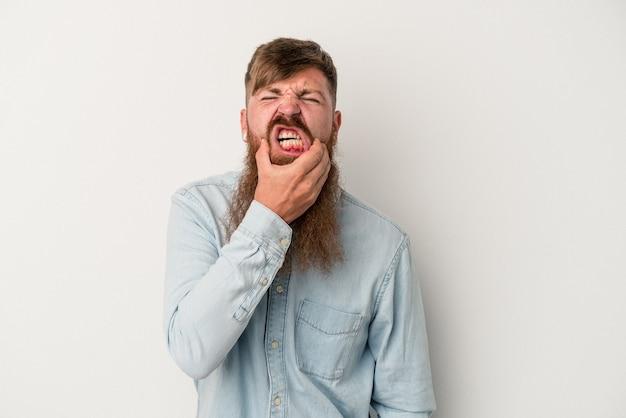 Joven jengibre caucásico con barba larga aislado sobre fondo blanco con un fuerte dolor de dientes, dolor de muelas.