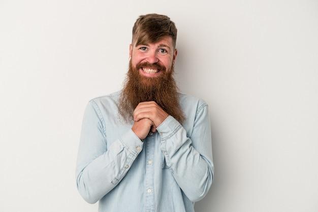 Joven jengibre caucásico con barba larga aislado sobre fondo blanco mantiene las manos debajo de la barbilla, está mirando felizmente a un lado.