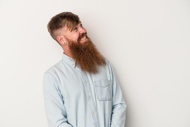 Joven jengibre caucásico con barba larga aislado sobre fondo blanco relajado y feliz riendo, cuello estirado mostrando los dientes.