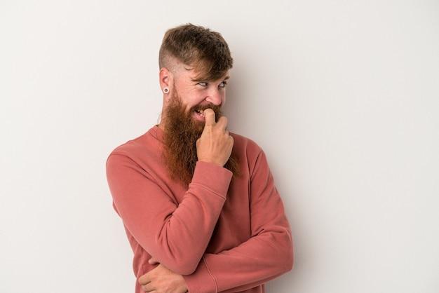 Joven jengibre caucásico con barba larga aislado sobre fondo blanco relajado pensando en algo mirando un espacio de copia.