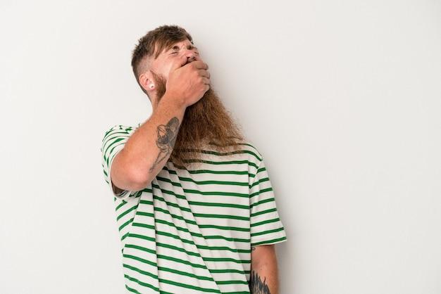 Joven jengibre caucásico con barba larga aislado sobre fondo blanco riendo feliz, despreocupada, natural emoción.