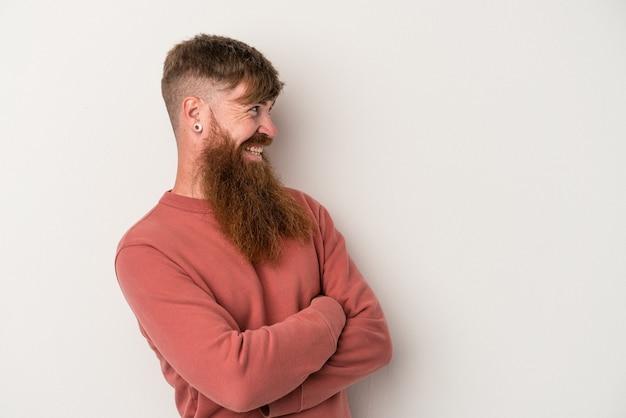 Joven jengibre caucásico con barba larga aislado sobre fondo blanco sonriendo confiado con los brazos cruzados.