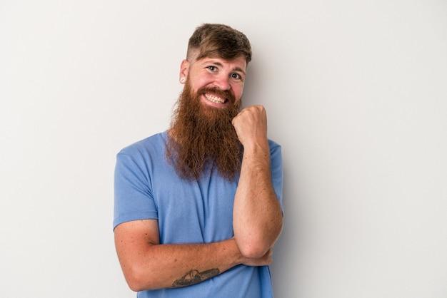 Joven jengibre caucásico con barba larga aislado sobre fondo blanco sonriendo feliz y confiado, tocando la barbilla con la mano.