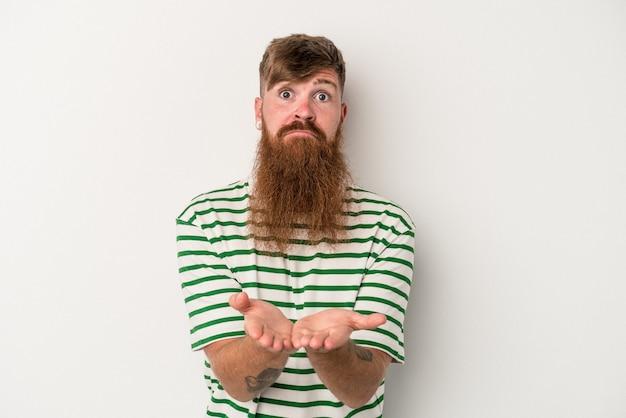 Joven jengibre caucásico con barba larga aislado sobre fondo blanco sosteniendo algo con las palmas, ofreciendo a la cámara.