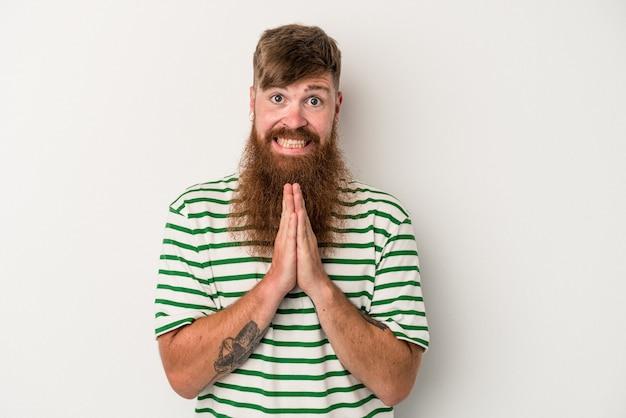 Joven jengibre caucásico con barba larga aislado sobre fondo blanco tomados de la mano en orar cerca de la boca, se siente confiado.