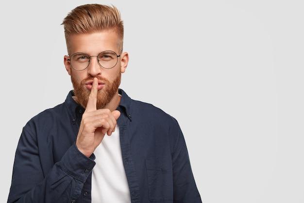 El joven jengibre secreto tiene una expresión misteriosa, toca los labios con el dedo índice, se viste informalmente, posa contra la pared blanca