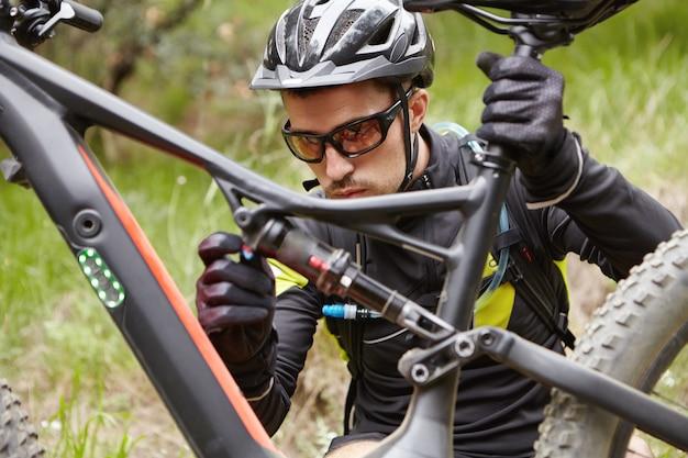 Joven jinete concentrado en casco, gafas y guantes sentado delante de su bicicleta de refuerzo