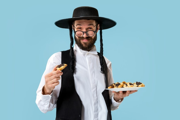 El joven judío ortodoxo con galletas hamantaschen para el festival purim. vacaciones, celebración, judaísmo, pastelería, tradición, galleta, concepto de religión