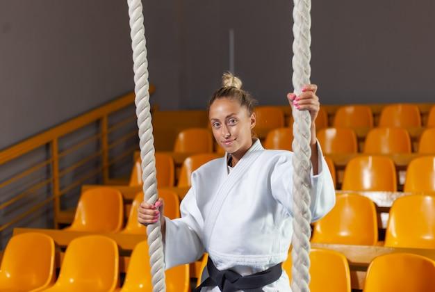 Joven judoka en kimono blanco y cinturón negro posando en el polideportivo