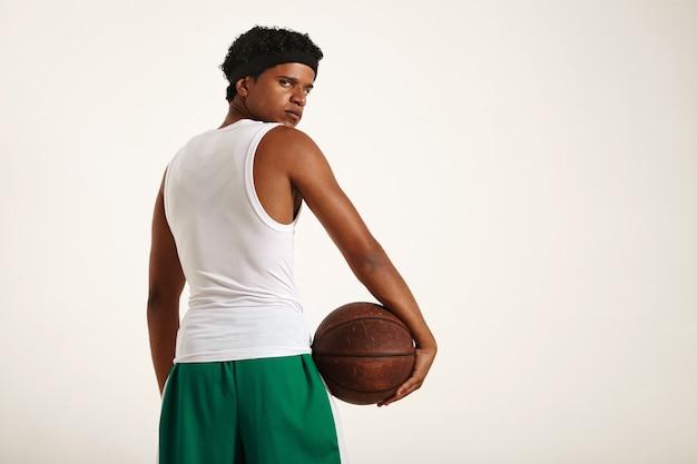 Joven jugador de baloncesto afroamericano serio decidido en uniforme blanco y verde con un afro corto sosteniendo una vieja pelota de baloncesto marrón en la cadera y mirando hacia atrás