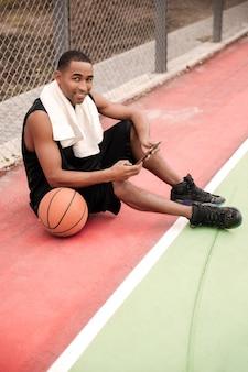 Joven jugador de baloncesto alegre sentado en el parque cerca de baloncesto y sosteniendo la tableta