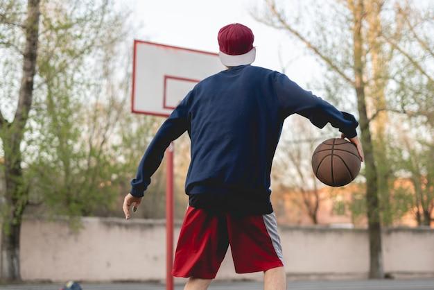 Joven jugador de baloncesto entrenando para driblar al aire libre en la cancha de asfalto