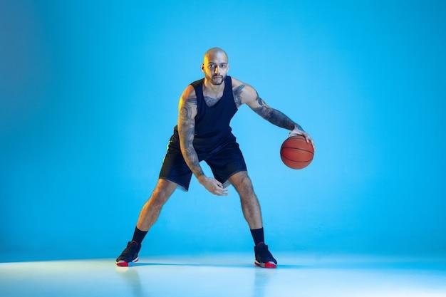 Joven jugador de baloncesto del equipo con entrenamiento de ropa deportiva, practicando en acción, movimiento aislado en la pared azul en luz de neón. concepto de deporte, movimiento, energía y estilo de vida dinámico y saludable.