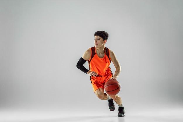 Joven jugador de baloncesto del equipo vistiendo ropa deportiva, practicando en acción, movimiento en marcha aislado sobre fondo blanco.