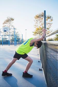 Joven jugador de baloncesto estirando las piernas antes de jugar al aire libre