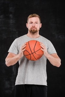 Joven jugador de baloncesto exitoso en ropa deportiva sosteniendo la pelota por el pecho mientras está de pie frente a la cámara
