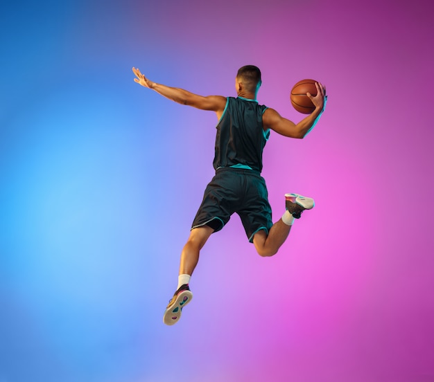 Joven jugador de baloncesto en movimiento sobre fondo de estudio degradado en luz de neón