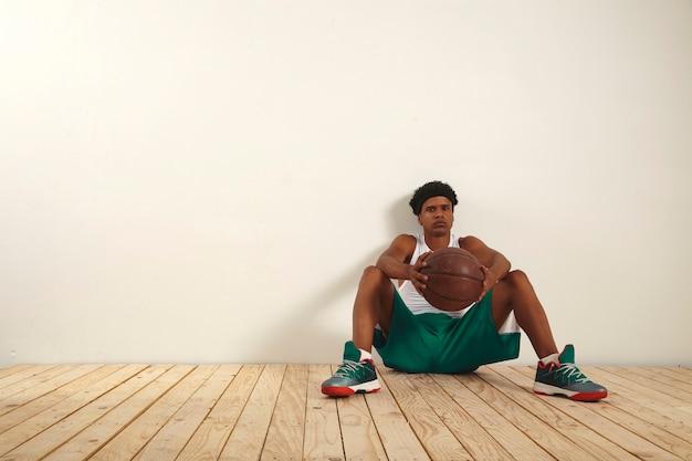 Joven jugador de baloncesto serio en pantalones cortos verdes y camisa blanca tomando un descanso contra una pared blanca sosteniendo una pelota de baloncesto grunge en sus manos
