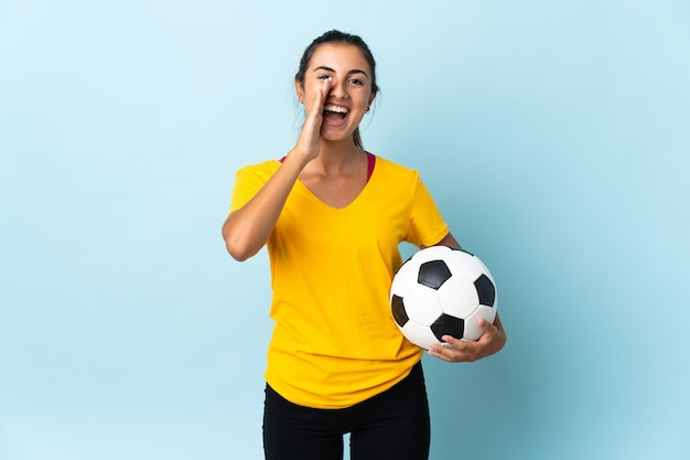 Joven jugador de fútbol hispano mujer sobre aislado en la pared azul gritando con la boca abierta