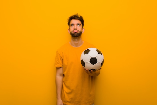 Joven jugador de fútbol hombre cansado y aburrido