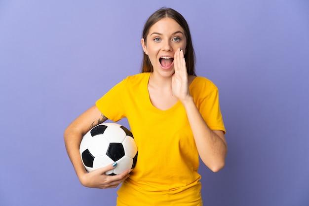 Joven jugador de fútbol lituano mujer aislada en la pared púrpura gritando con la boca abierta
