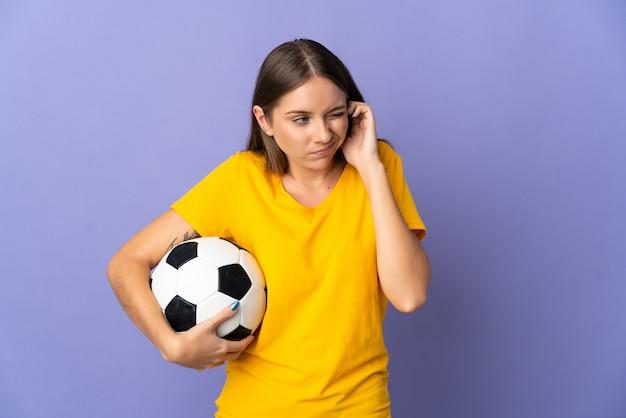 Joven jugador de fútbol lituano mujer aislada sobre fondo púrpura frustrado y cubriendo las orejas