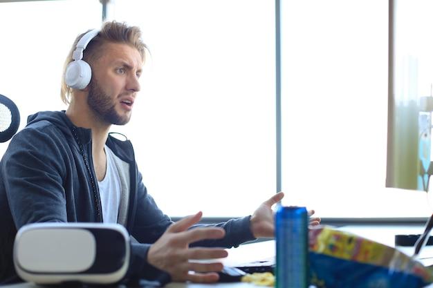 Joven jugador molesto jugando videojuegos en línea en la computadora y se siente deprimido.