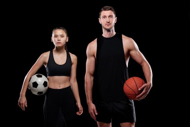 Joven jugadora de fútbol y baloncesto masculino en ropa deportiva sosteniendo bolas mientras está de pie