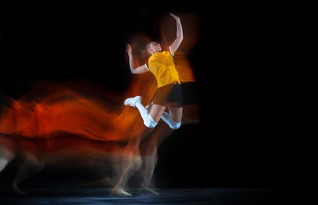 Joven jugadora de voleibol en estudio negro con luz mixta.