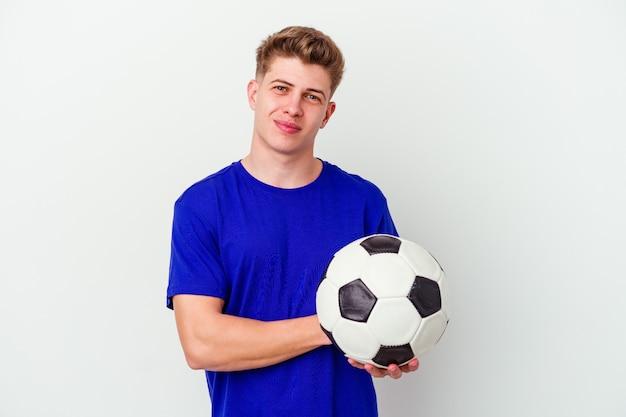 Joven jugando al fútbol aislado en la pared riendo y divirtiéndose