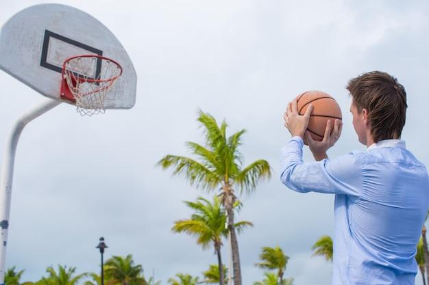 Joven jugando baloncesto afuera en el exótico resort